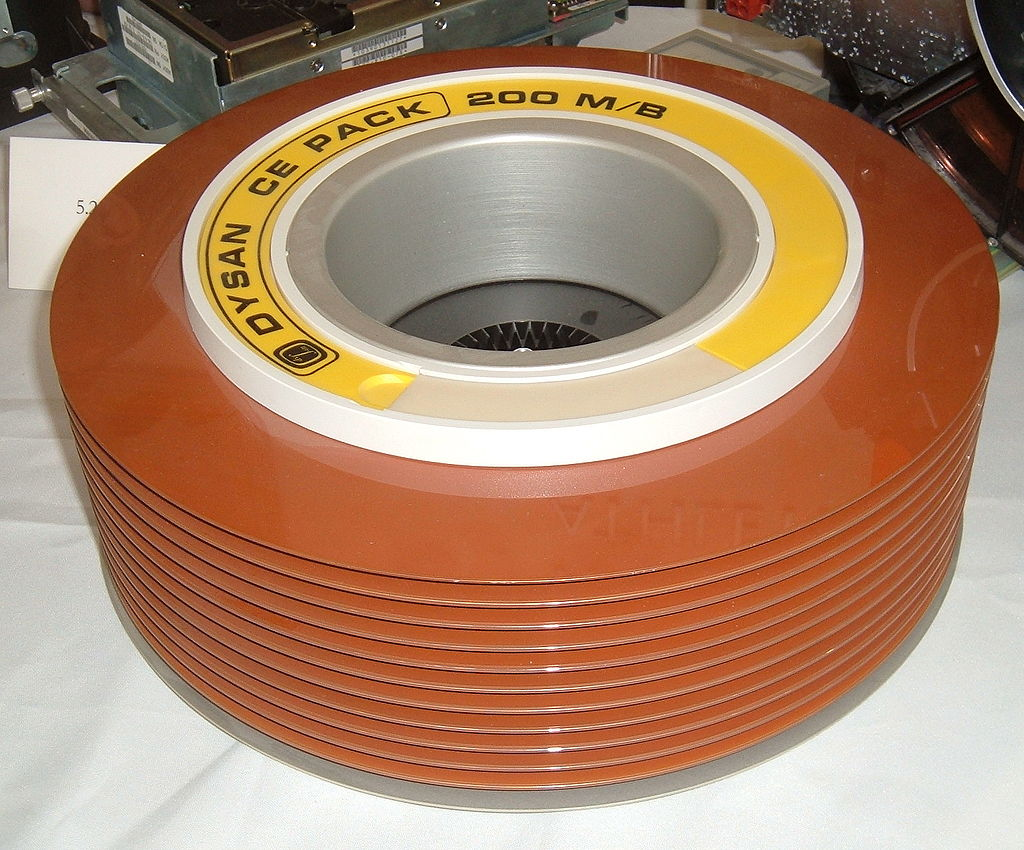 A stack of old hard disks used before the 1980s. Note the brown magnetic oxide color of the disks. Several disks were required in one pack to have a reasonable amount of storage capacity.