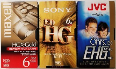 Blank VHS videotape brands from Maxell, Sony, and JVC in the T-120 length format.