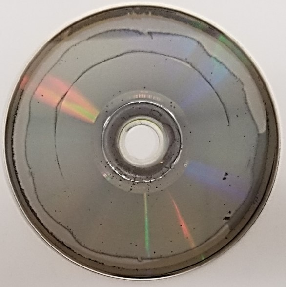 Laser rot or disc rot on a DVD movie disc. The metal of the DVD disc has oxidized and caused the formation of holes in the metal as well as non-uniformity and thinning of the metal layer.
