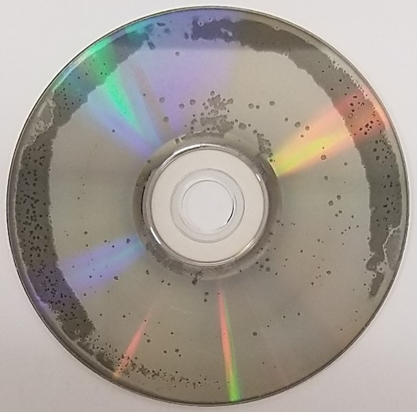 Disc rot or laser rot on a DVD movie disc. Spots of missing metal layer are present as well as discoloration of the metal, especially on the outer portion of the DVD.