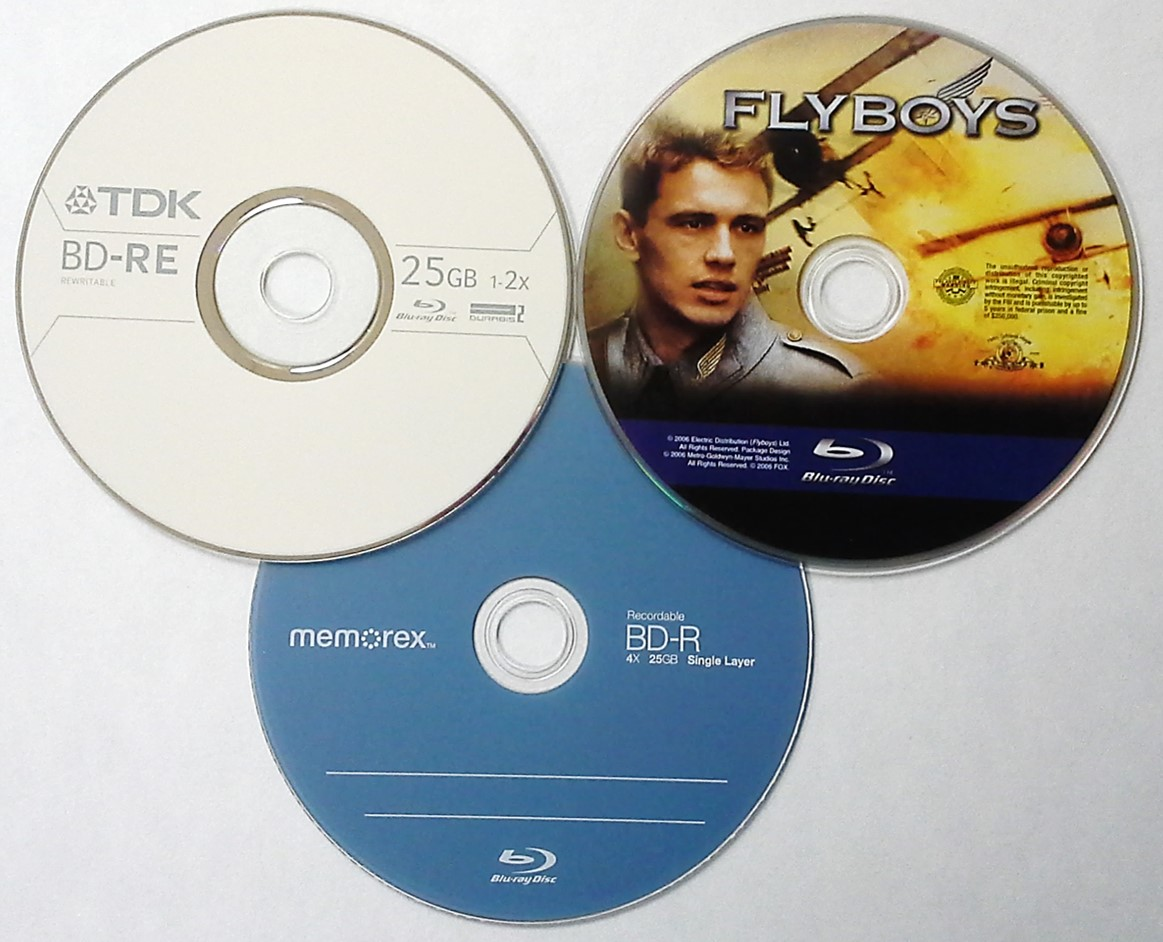 Three different types of Blu ray disk formats. Shown is a Blu-ray movie disc (Flyboys), a 4x BD-R or recordable Blu-ray from Memorex and a 25 GB rewritable Blu-ray or BD-RE from TDK.