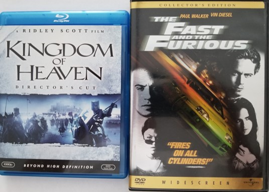 A Blu-ray movie disc (Kingdom of Heaven) and DVD movie disc (The Fast and the Furious), both of which may contain hidden Blu-ray and DVD Easter eggs.