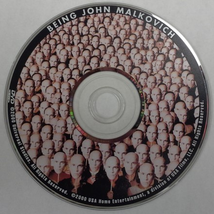 A DVD movie disc, Being John Malkovich. This is a single-sided dual-layer disc and therefore, a label is permitted on the top surface of the DVD.