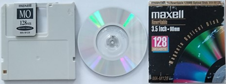 A Maxell 3.5-inch and 128 MB rewritable magneto-optical disk or MO disk shown outside of it's cartridge and with exterior packaging.