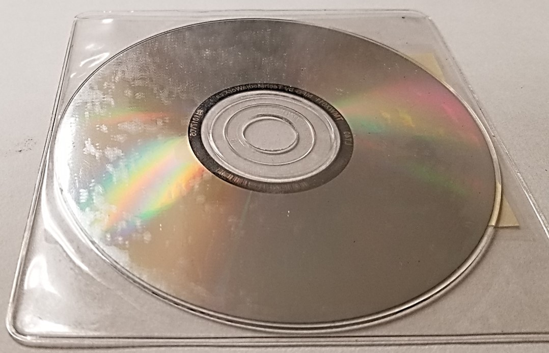 Plastic storage sleeve for CDs, DVDs, or Blu-ray discs that has chemically degraded and left a deposit on the surface of the CD stored inside of it.