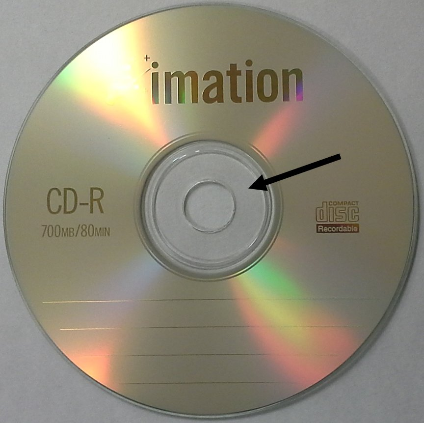 Clear hub area of a CD-R disc by Imation indicated by the black arrow. When labeling optical discs with a marking pen, it is best to only write in this area to prevent possible disc damage.