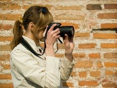 A woman taking digital photographs with a digital camera and using tips for taking great digital photograph.