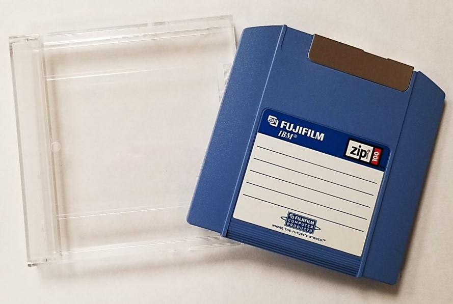 Zip disk 100 MB from Fujifilm and its plastic storage case, which provides protection from dust, debris, and physical damage.